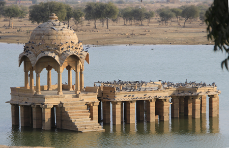 arched: Arched stone gallery on pillared platform in Gadisar Lake, Jaisalmer, Rajasthan, India, Asia Stock Photo