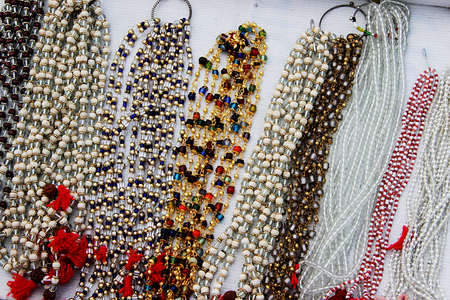 beaded: Display of variety of colorful, white and transparent beaded necklaces