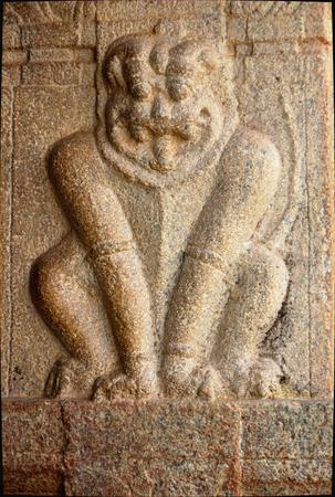 nandi: Humorous sitting posture of lion on stone pillar at Narasimha Temple in Nandi Hills near Bengaluru, Karnataka, India, Asia