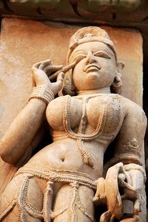 madhya pradesh: Statue of beautiful lady engaged in the act applying Kajal (collyrium) in her eye at Jain Temple in Khajuraho, Madhya Pradesh, India, Asia