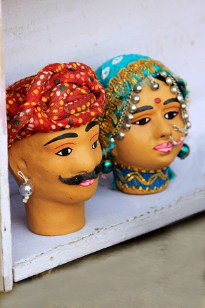 customary: Colorful terracotta faces of Rajasthani couple draped in traditional attire on display at Gadisar Lake, Jaisalmer, Rajasthan, India, Asia