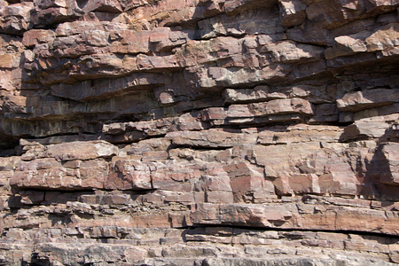 rock strata: Closer view of sunlit strata of brownish rock face