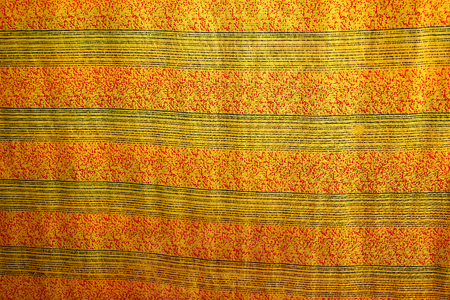 Fabric print design having yellow-black stripes with red sprinkled dots in between