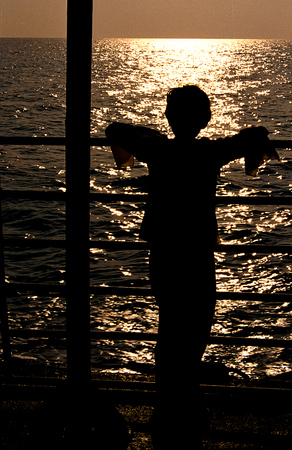 tinge: Curious girl watching golden tinge of reflected sun rays of setting sun from ship deck