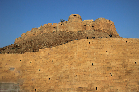 Fort situated on top of earthen hill with stone wall in foreground at Jaisalmer, Rajasthan, India, Asia Stock Photo