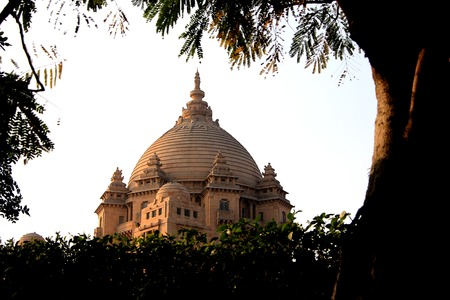 View of central dome of Umaid Bhavan Palace framed by foliage at sunset in Jodhpur, Rajasthan, India, Asia