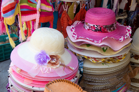 array: Array of pink and white hats on display at roadside store