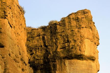 Huge rocky walls soaked in golden yellow morning sunlight at Badami, Karnataka, India, Asia