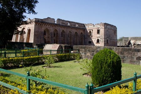 View of park and Hindola Mahal or Swinging Palace with sloping side walls at Mandu in Madhya Pradesh, India, Asia
