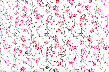 Delicate design of red flowers and green stems and leaves on white cotton fabric Stock Photo
