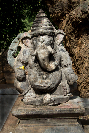 Ancient statue of Ganesha on stone pedestal under tree at Mahkoota, District Bagalkot, Karnataka, India, Asia