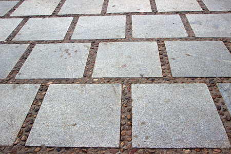 Layout of dressed rectangular grey, granular, granite stone slabs on pavement