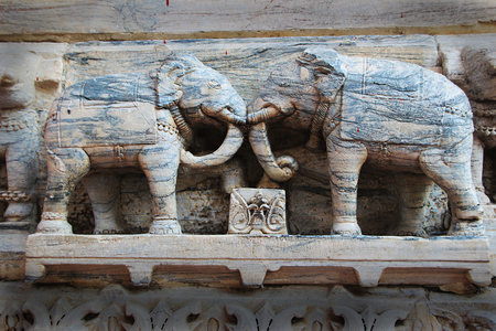 Attractive, grainy, stone statues of elephants in combat mood at Jagadeesh Temple in Udaipur, Rajasthan, India, Asia