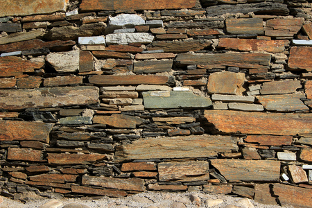 Wall built up of neatly laid out layers of flat stone blocks with various lengths and thicknesses. Stock Photo