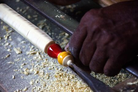 View of craftsman engaged in polishing a spinning woodcraft