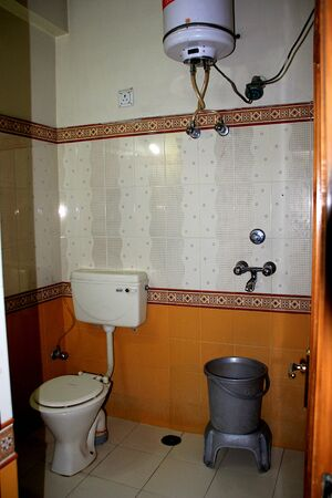 View of inside of modern bathroom with commode, geyser, tiled walls, floor and other accessories