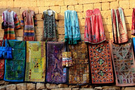Mats, dresses and bags with bold colored designs displayed on walls at Jaisalmer Fort in Jaisalmer, Rajasthan, India, Asia