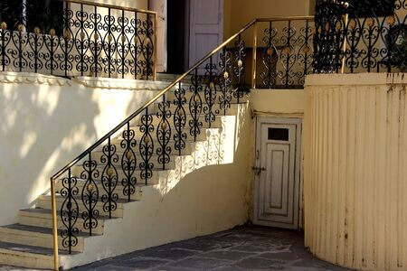 Beautifully designed and painted iron railings and latched basement door