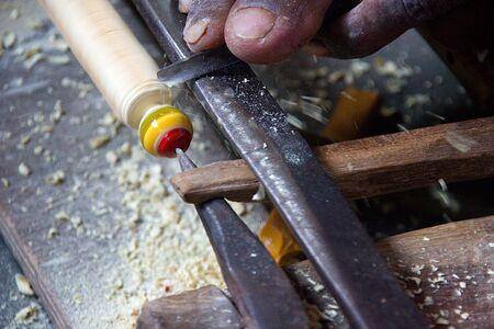Skilled village artisan busy in making a wooden toy at Madhu Vana near Bengaluru, Karnataka, India, Asia