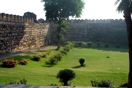Cool look of trimmed green grass lawn and bushes inside walls of  fort at Jhansi in Uttar Pradesh, India, Asia
