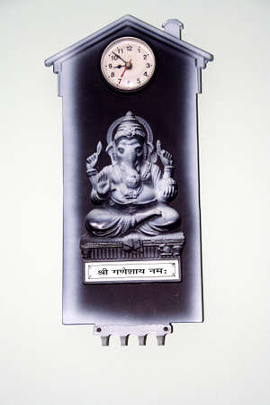Plaque made of Bakelite with clock and image of Ganesha hung on white wall