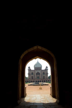 Historical monument of Safdarjung Tomb at New Delhi viewed through door arches at entrance, India, Asia