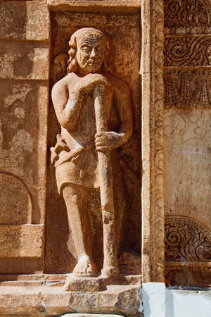 Stone sculpture of man holding long stick at Kumaraswamy Temple in Nandihalli near Sandur, District Belllary, Karnataka, India, Asia