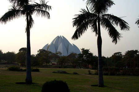Top of Lotus Temple or Bahai House of Worship viewed between two trees at garden in Delhi, India, Asia