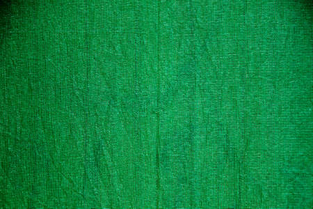 Close-up view of dark green, woven jute fabric with coarse grain structure