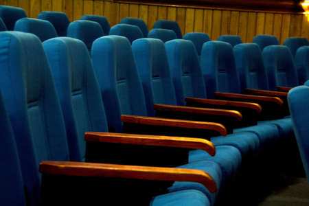 Rows of blue colored cushioned seats with arm rests at convention hall Standard-Bild