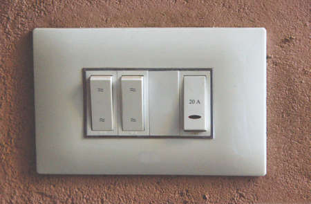 View of exquisite, neat, modern, white switch board fitted on pink colored wall Standard-Bild