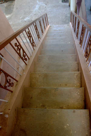 View looking down of concrete steps and iron railings of staircase