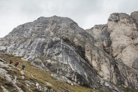 Tourist in Dolomites alps crossing rocks,  Italian Alps