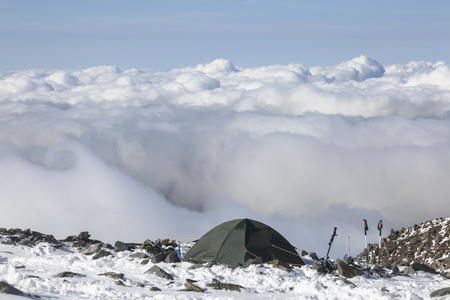 Hiking tent in the French Alps. Over the clouds. Idyllic adventure vacations. Scenic image of hiking concept. Perfect moment in alpine highlands. Location Mont Blanc, France.