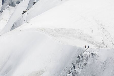 Tied climbers climbing mountain with snow field in the French Alps, Chamonix-Mont-Blanc, France