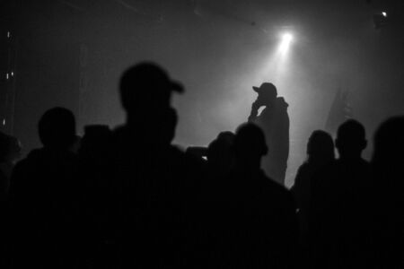 A silhouette of singer rap musician during live concert in dark light. Dark background, smoke, spotlights