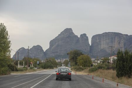 The car goes on the road to Meteora, Greece. Stone mountains ahead