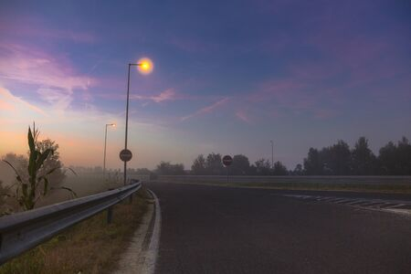 Highway without cars, light lanterns and pink gentle sky at dawn