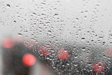 Rainy weather, drops on a car window and red stop lights ahead