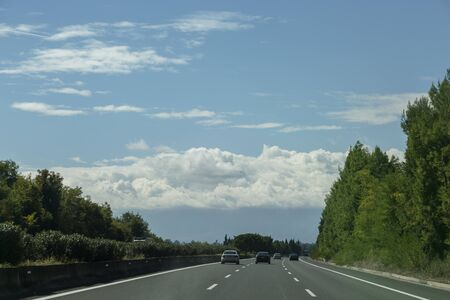 The highway is surrounded by green trees, blue sky and cumulus clouds ahead Stock Photo