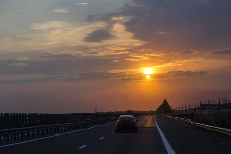 Road trip at sunset, orange sky in the evening, a car on the road Stock Photo