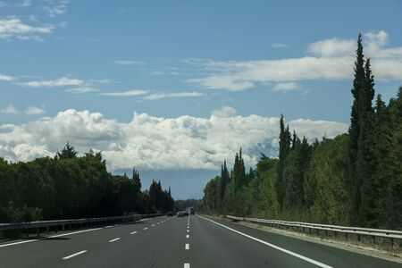 The highway in Greece is surrounded by green trees, blue skies and cumulus clouds ahead