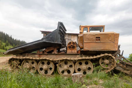 Big old bulldozer in the woods. Vintage tractor with caterpillars, Carpathians, Ukraine Stock Photo