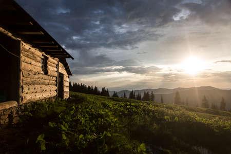 Evening sunbeams shine on a wooden house in the mountains. Carpathians, Marmaroshchyna, Maramures, Ukraine