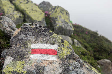 Marking the tourist route painted on stones in red and white. Travel route sign in the Carpathians mountains Stock Photo
