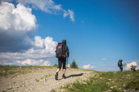 two hikers follow a path, the blue sky on the horizon. Hiking travel outdoor concept panoramic view