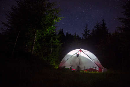Illuminated camp tent at night. Dark night sky with stars breaking through the forest.