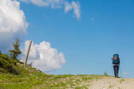 hiker follows a path, the blue sky on the horizon. Hiking travel outdoor concept in mountains