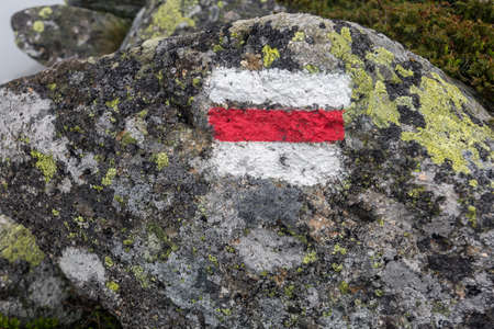 Tourist route mark on stone, painted in white and red guiding the way to the hiking mountain