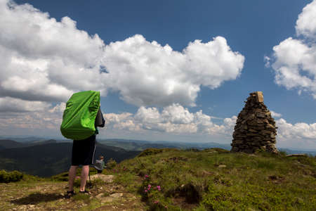 Mountains stone stack and tourists follow the path, the blue sky on the horizon. Hiking travel outdoor concept panoramic view
